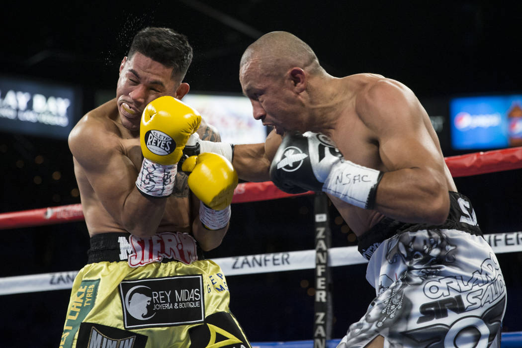 Miguel Roman, left, takes a punch from Orlando Salido in the super featherweight boxing bout at the Mandalay Bay Events Center in Las Vegas, Saturday, Dec. 9, 2017. Roman won by way of techni ...