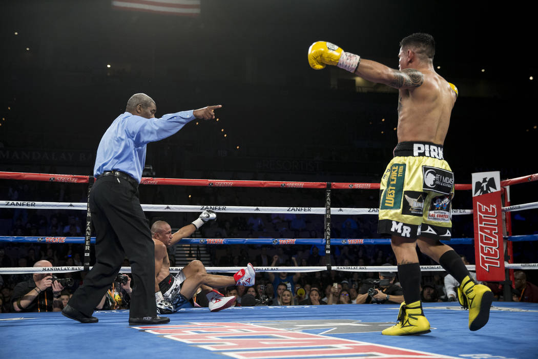 Miguel Roman, right, walks to his corner after knocking down Orlando Salido in the super featherweight boxing bout at the Mandalay Bay Events Center in Las Vegas, Saturday, Dec. 9, 2017. Roman won ...