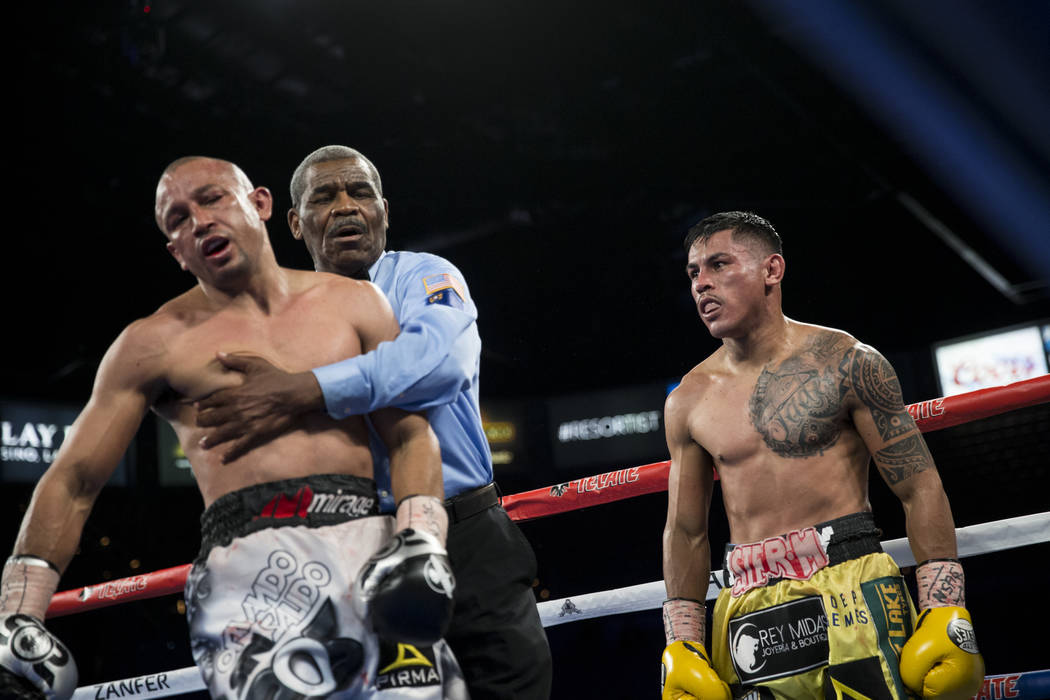 Orlando Salido, left, after the sound of the bell in between rounds in his fight against Miguel Roman in the super featherweight boxing bout at the Mandalay Bay Events Center in Las Vegas, Saturda ...