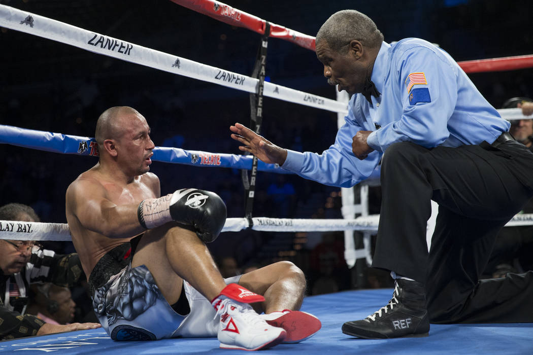 Orlando Salido, left, gets a count after getting knocked down against Miguel Roman in the super featherweight boxing bout at the Mandalay Bay Events Center in Las Vegas, Saturday, Dec. 9, 2017. Ro ...