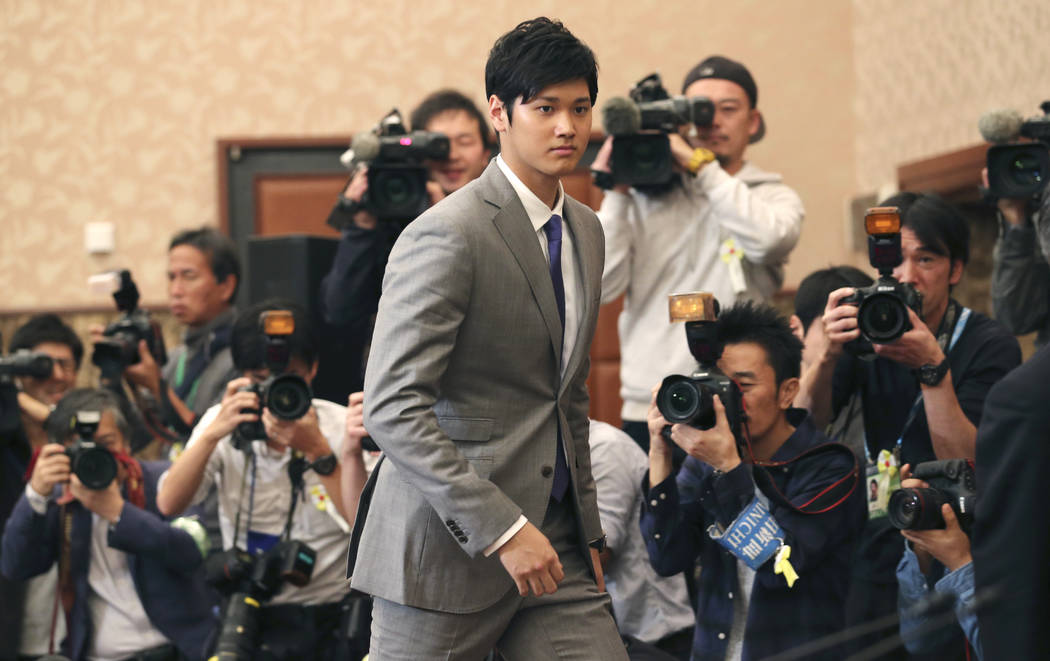 In this Nov. 11, 2017, file photo, Japanese pitcher-outfielder Shohei Ohtani arrives for a press conference at the Japanese National Press Center in Tokyo. Japanese star Shohei Ohtani is bringing  ...