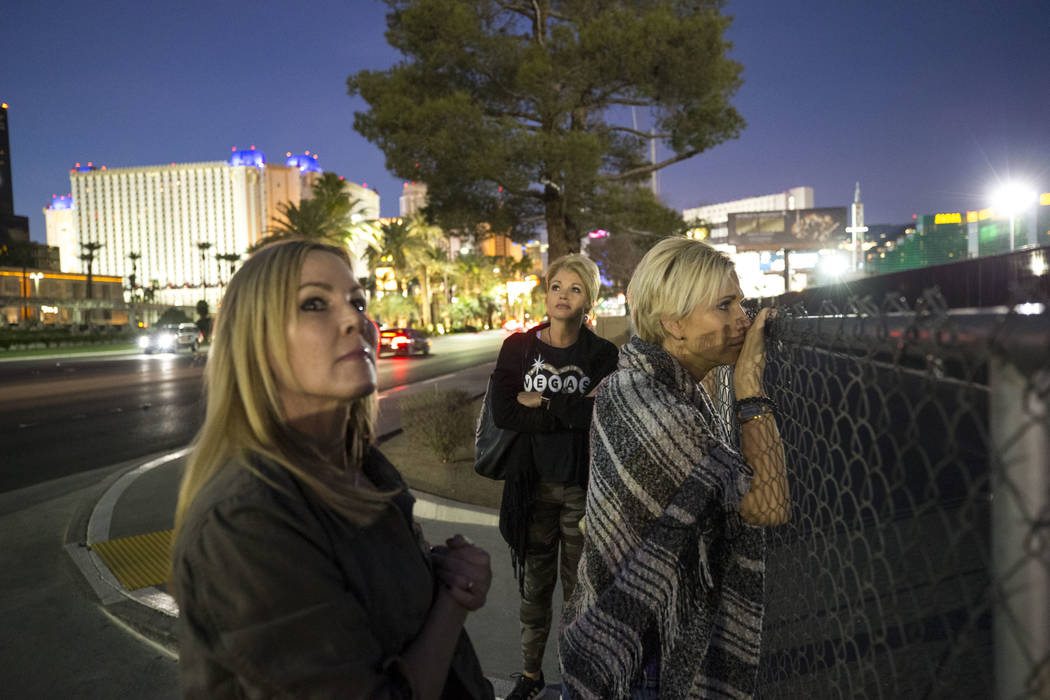 Route 91 Harvest survivors Kim Yeazel, from left, Tina Cartwright and Michelle McGinn visit the Las Vegas Village festival grounds, Monday, Dec. 18, 2017, the site of the Oct, 1 shooting. The frie ...