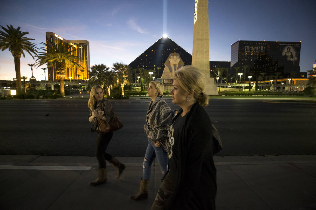 Route 91 Harvest survivors Kim Yeazel, from left, Michelle McGinn and Tina Cartwright walk by the Las Vegas Village festival grounds, Monday, Dec. 18, 2017, the site of the Oct, 1 shooting. The fr ...