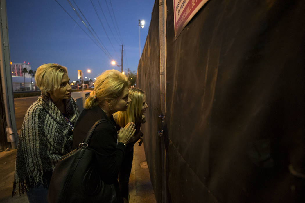Route 91 Harvest survivors Michelle McGinn, from left, Tina Cartwright and Kim Yeazel looks through the fence at the Las Vegas Village festival grounds, Monday, Dec. 18, 2017, the site of the Oct, ...
