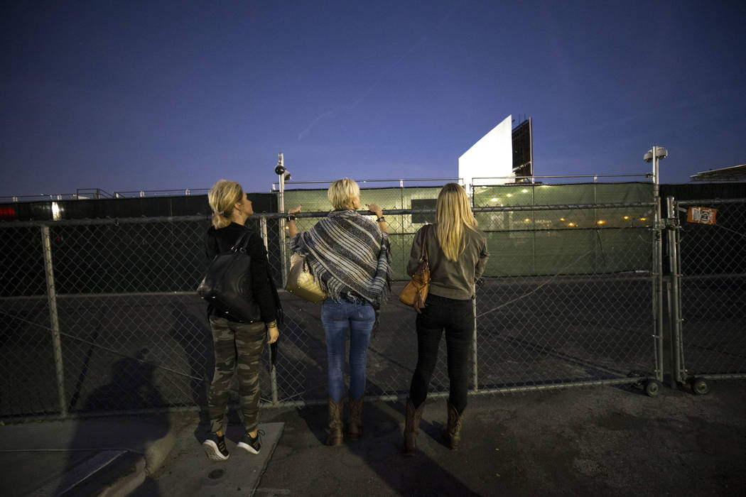 Route 91 Harvest survivors Tina Cartwright, from left, Kim Yeazel and Michelle McGinn looks through the fence at the Las Vegas Village festival grounds, Monday, Dec. 18, 2017, the site of the Oct. ...