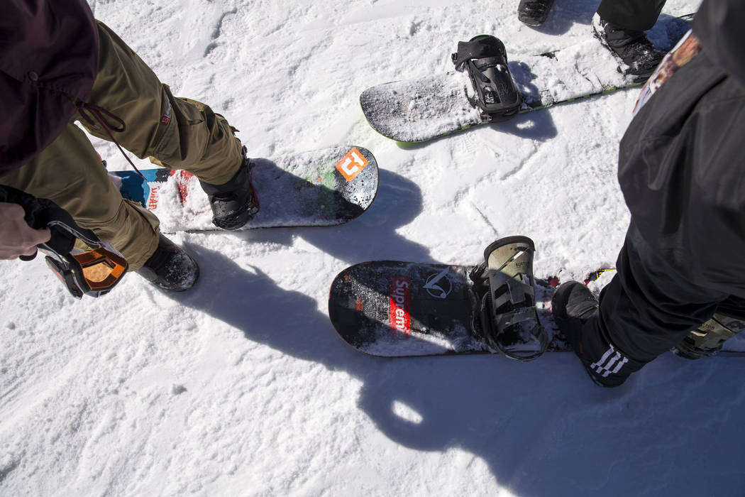 Snowboarders prepare to strap in before taking a ride down the bunny hill on Friday afternoon, Dec. 8, 2017, at  Lee Canyon opening day. Richard Brian Las Vegas Review-Journal @vegasphotograph
