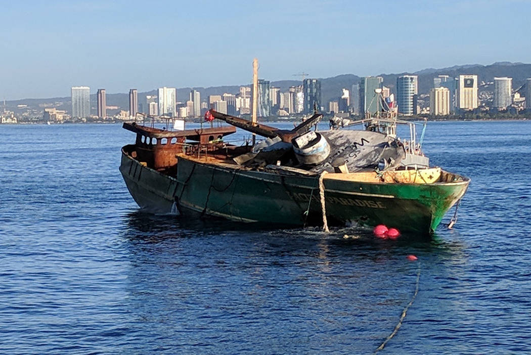 The Pacific Paradise, a commercial fishing vessel carrying foreign workers that ran aground and later burned and leaked fuel just off the beaches of Waikiki, Hawaii is towed out to sea Thursday, D ...