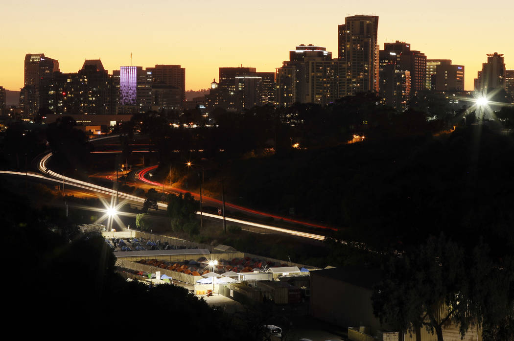 The city-sanctioned tent encampment, below, sits on the edge of Balboa Park as the sun sets behind buildings downtown in San Diego in October. (AP Photo/Gregory Bull)