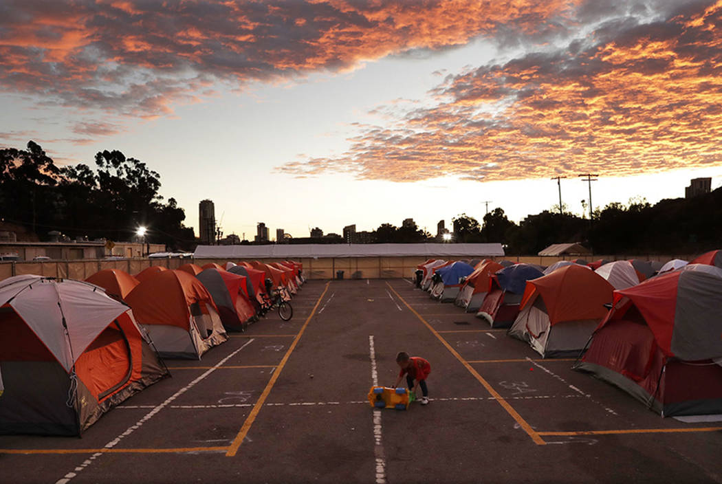 A boy plays as the sun sets over donated tents for homeless families lined up on a parking lot in the city-sanctioned encampment in San Diego. (AP Photo/Gregory Bull)