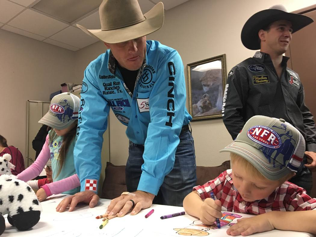 Caleb Smidt looks on as 4-year-old Tristan Duenez shows off his coloring skills during an event Friday partnering the Wrangler National Finals Rodeo with the Grant a Gift Autism Foundation. Patric ...
