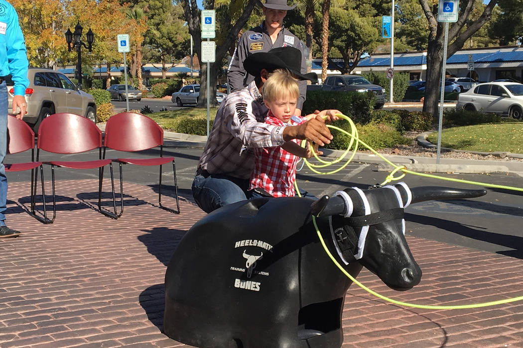 Four-year-old Tristan Duenez gets an assist from all-around world champion cowboy Junior Nogueira in roping a practice steer head Friday during an event partnering the Wrangler National Finals Rod ...