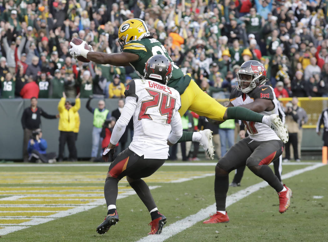 Green Bay Packers' Aaron Jones leaps in the end zone for a touchdown during overtime of an NFL football game against the Tampa Bay Buccaneers Sunday, Dec. 3, 2017, in Green Bay, Wis. The Packers w ...