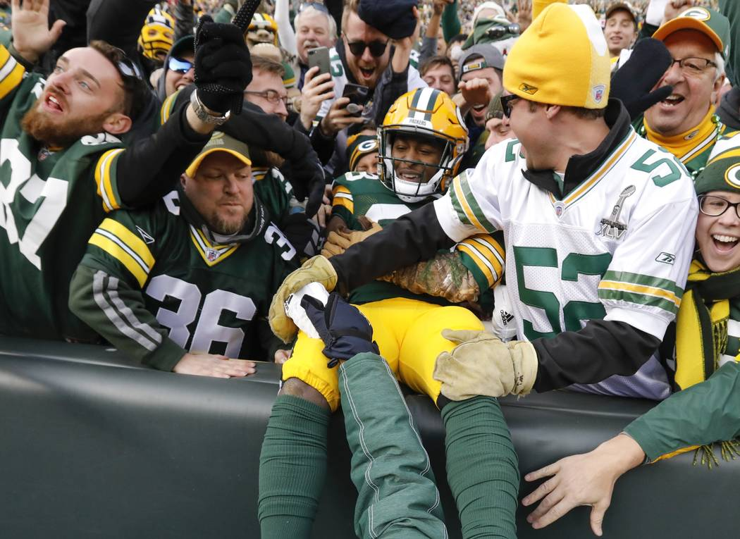 Green Bay Packers' Aaron Jones celebrates his touchdown run with fans during overtime of an NFL football game against the Tampa Bay Buccaneers Sunday, Dec. 3, 2017, in Green Bay, Wis. The Packers  ...