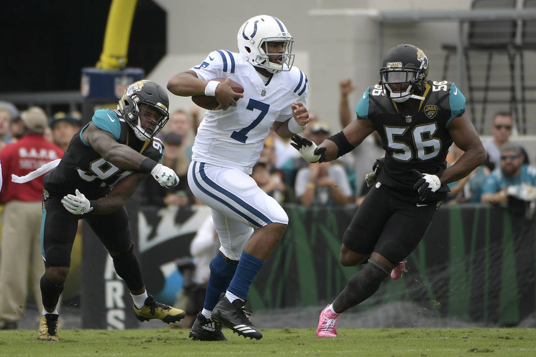 Indianapolis Colts quarterback Jacoby Brissett (7) scrambles between Jacksonville Jaguars defensive end Yannick Ngakoue (91) and defensive end Dante Fowler (56) during the first half of an NFL foo ...