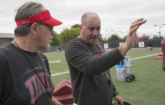 UNLV Rebels coach Tony Sanchez, right, discusses a play with defensive coordinator Kent Baer between plays during team practice at the Bill 'Wildcat' Morris Rebel Park field on Tuesday, Sept. 20,  ...