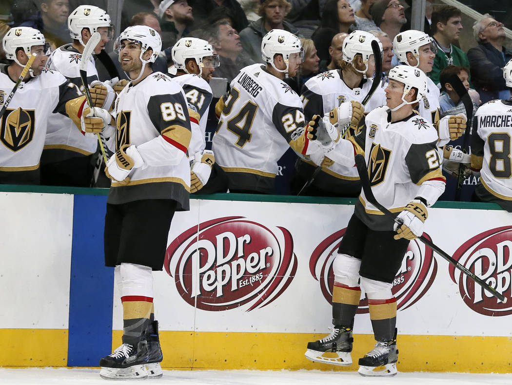 Vegas Golden Knights right wing Alex Tuch (89) and Cody Eakin, right, are congratulated by the bench after a goal by Tuch during the first period of an NHL hockey game against the Dallas Stars on  ...