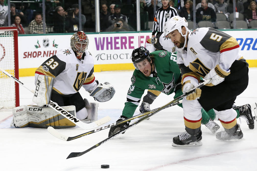 Vegas Golden Knights' Maxime Lagace (33) and Dallas Stars right wing Brett Ritchie (25) watch as defenseman Deryk Engelland (5) clears a puck from in front of the net during the first period of an ...