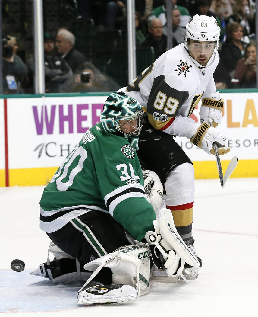 Dallas Stars goalie Ben Bishop (30) deflects a shot as Vegas Golden Knights right wing Alex Tuch (89) watches during the second period of an NHL hockey game, Saturday, Dec. 9, 2017, in Dallas. (AP ...
