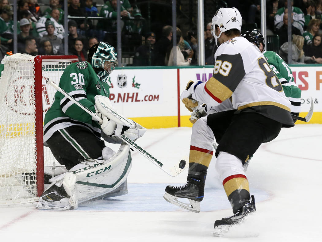 Dallas Stars goalie Ben Bishop (30) blocks a shot as Vegas Golden Knights right wing Alex Tuch (89) looks for a rebound during the second period of an NHL hockey game Saturday, Dec. 9, 2017, in Da ...
