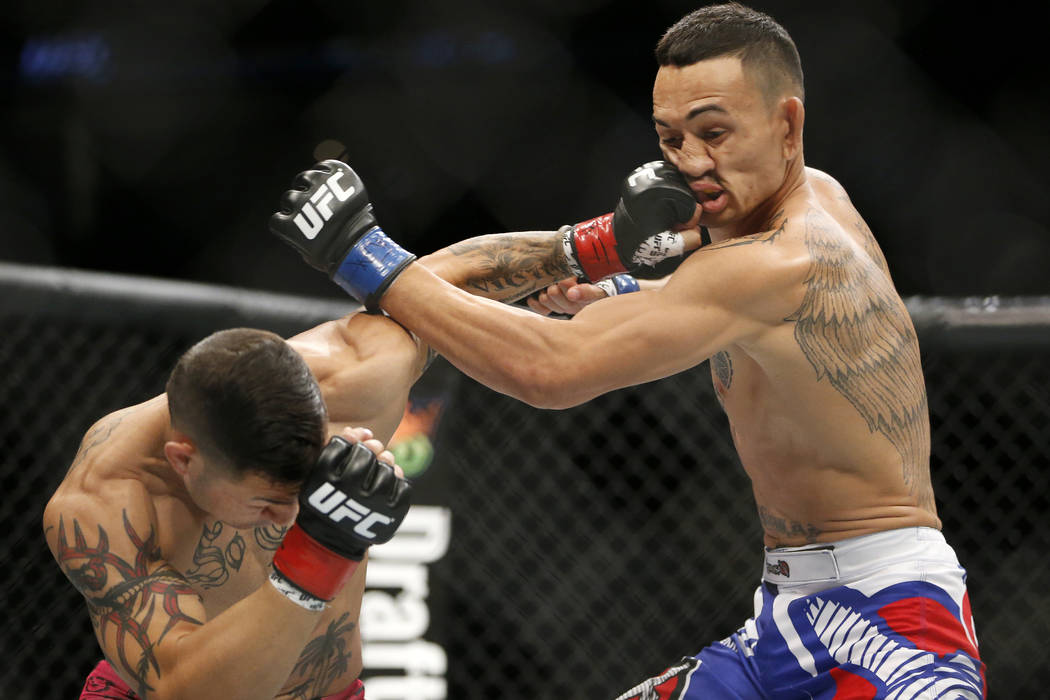 Cub Swanson, left, lands a punch on Max Holloway during a UFC mixed martial arts bout, Saturday, April 18, 2015, in Newark, N.J. (AP Photo/Julio Cortez)