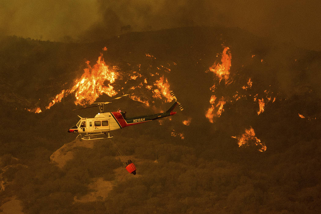 A helicopter carries water while trying to keep a wildfire from jumping Santa Ana Rd. near Ventura, Calif., on Saturday, Dec. 9, 2017. (AP Photo/Noah Berger)