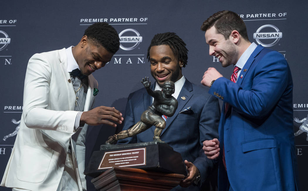 Heisman Trophy finalists, from left, Louisville quarterback Lamar Jackson, Stanford running back Bryce Love and Oklahoma quarterback Baker Mayfield look at the trophy during a media event Saturday ...