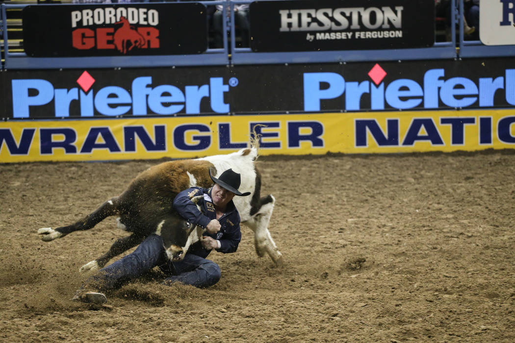 Tanner Milan of Cochrane, Alberta wrestles a steer during the third night of the 59th Wrangler National Finals Rodeo at the Thomas & Mack Center in Las Vegas, Saturday, Dec. 9, 2017. Joel Ange ...
