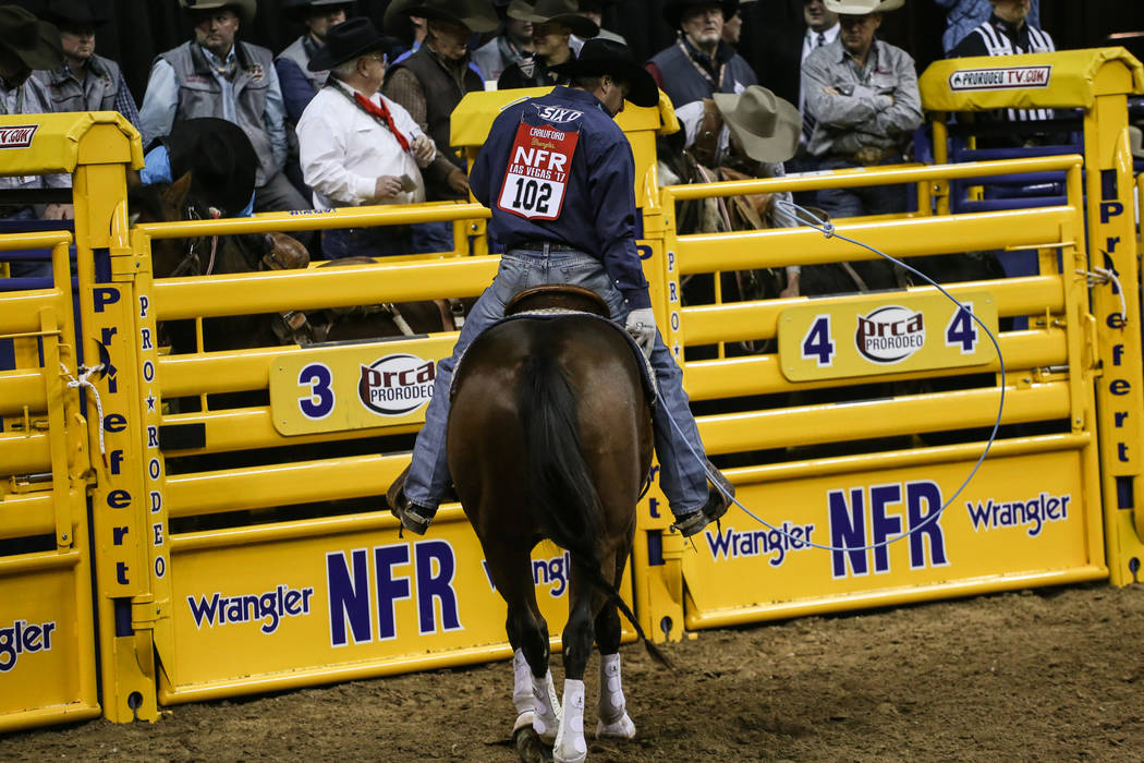 Charly Crawford of Prineville, Ore. rides away after the team roping event during the third night of the 59th Wrangler National Finals Rodeo at the Thomas & Mack Center in Las Vegas, Saturday, ...