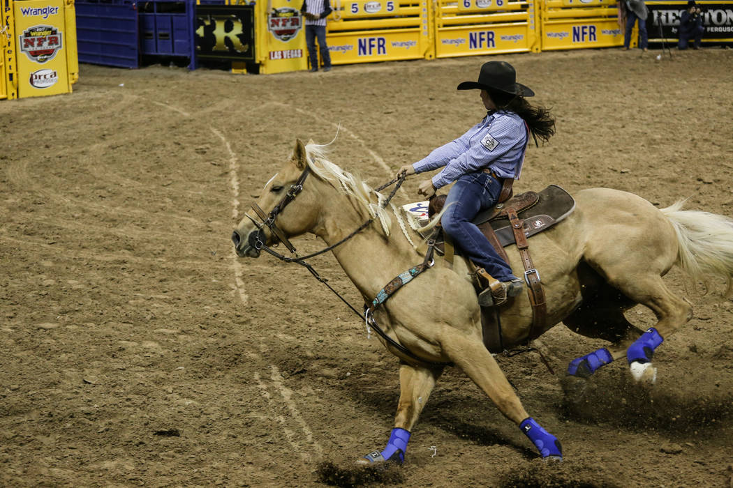 Hailey Kinsel of Cotulla, Texas turns a corner in the barrel racing event during the third night of the 59th Wrangler National Finals Rodeo at the Thomas & Mack Center in Las Vegas, Saturday,  ...