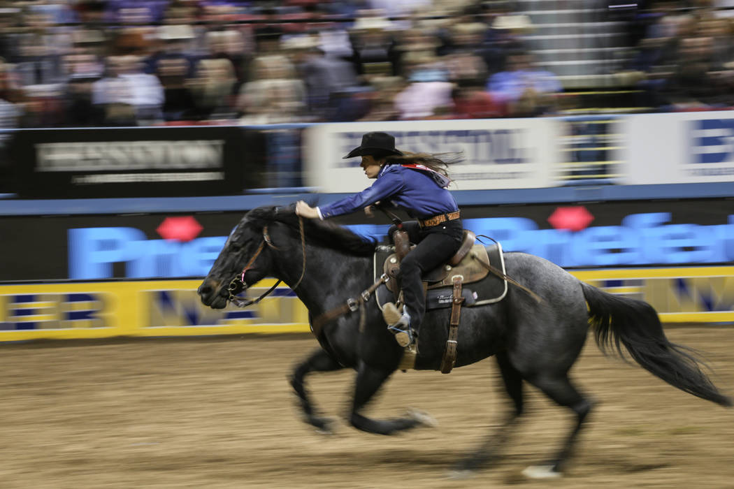 Nellie Miller of Cottonwood, Calif. rides in the barrel racing event during the third night of the 59th Wrangler National Finals Rodeo at the Thomas & Mack Center in Las Vegas, Saturday, Dec.  ...