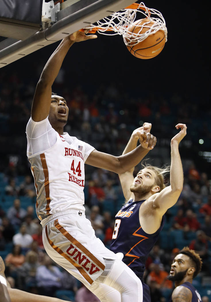UNLV's Brandon McCoy dunks over Illinois' Michael Finke during the first half of an NCAA college basketball game Saturday, Dec. 9, 2017, in Las Vegas. (AP Photo/John Locher)