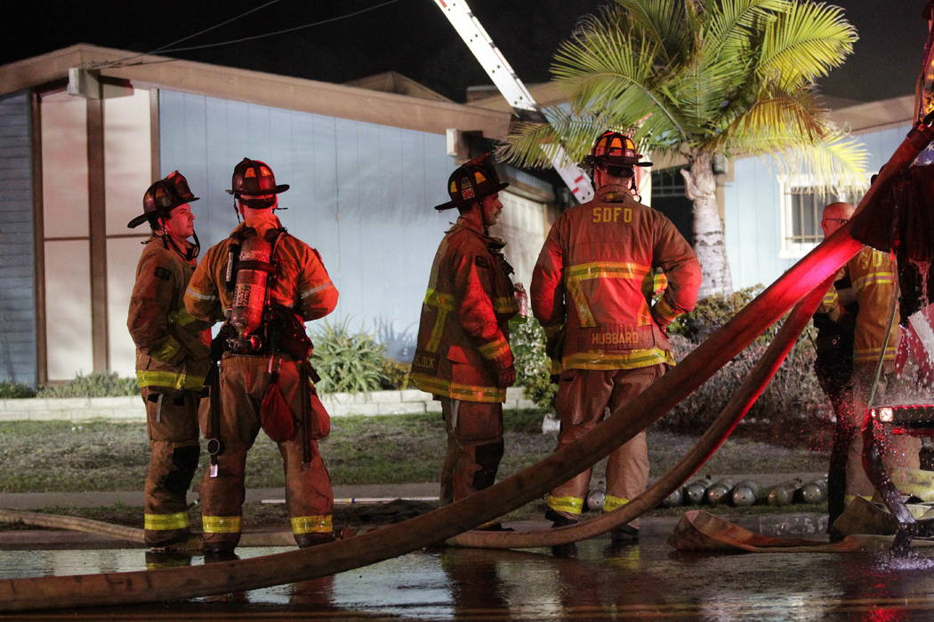 Firefighters stand in front of the house where a small plane crashed into it in San Diego, Saturday, Dec. 9, 2017.  (Hayne Palmour IV/The San Diego Union-Tribune via AP)