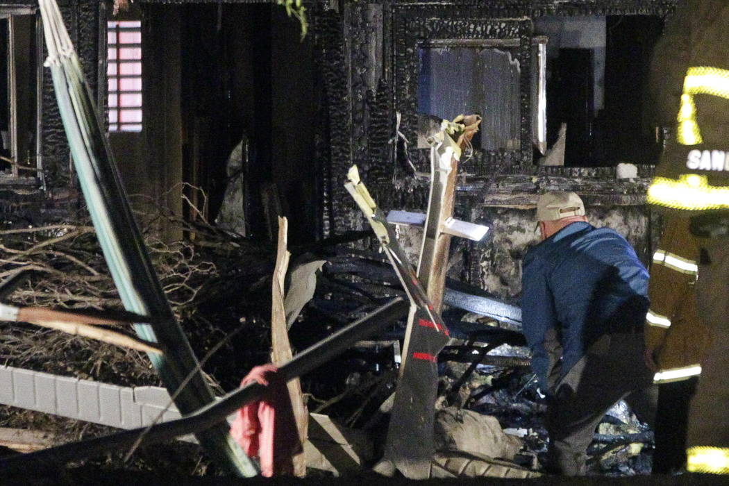 An investigator, standing next to the tail section, looks at the charred remains of a small plane that crashed into a house that was damaged by fire after the plane hit the house in San Diego, Sat ...