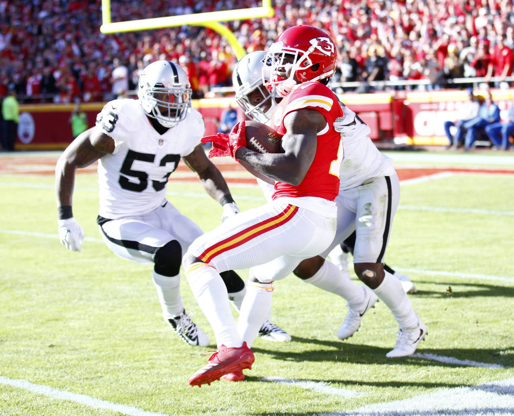 Kansas City Chiefs wide receiver Tyreek Hill (10) makes a catch along the sideline as Oakland Raiders middle linebacker NaVorro Bowman (53) and cornerback T.J. Carrie (38) defend during the first  ...