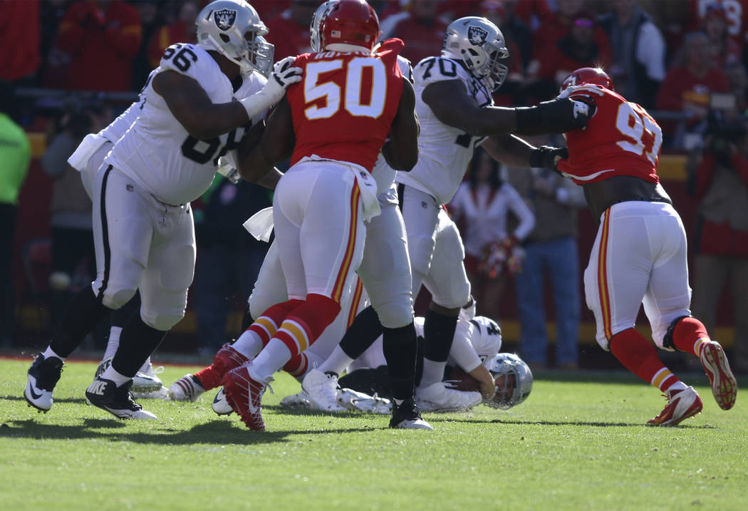 Oakland Raiders quarterback Derek Carr (4) is sacked by Kansas City Chiefs defensive end Chris Jones (95) during the first half of a NFL game in Kansas City, Mo., Sunday, Dec. 10, 2017. Heidi Fang ...