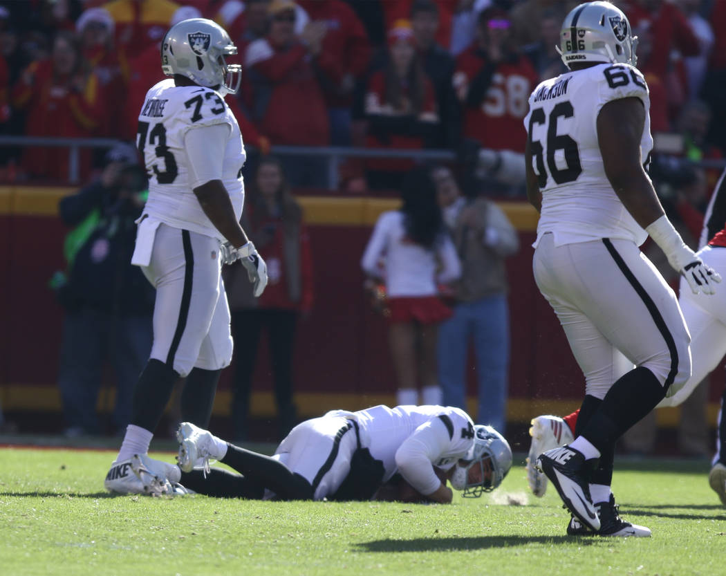 Oakland Raiders quarterback Derek Carr (4) remains on the field after being sacked by Kansas City Chiefs defensive end Chris Jones (95) during the first half of a NFL game in Kansas City, Mo., Sun ...