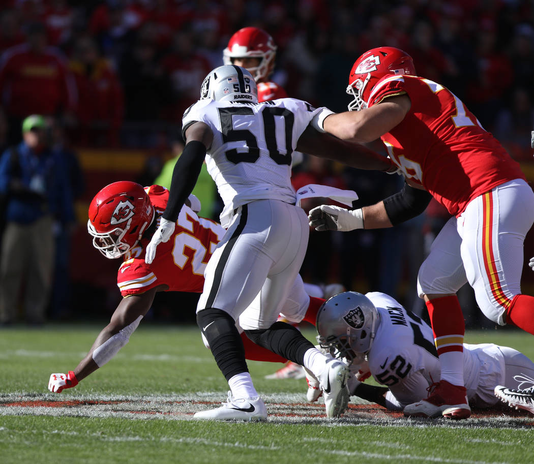 Oakland Raiders defensive end Khalil Mack (52) tackles Kansas City Chiefs running back Kareem Hunt (27) during the first half of a NFL game in Kansas City, Mo., Sunday, Dec. 10, 2017. Heidi Fang L ...