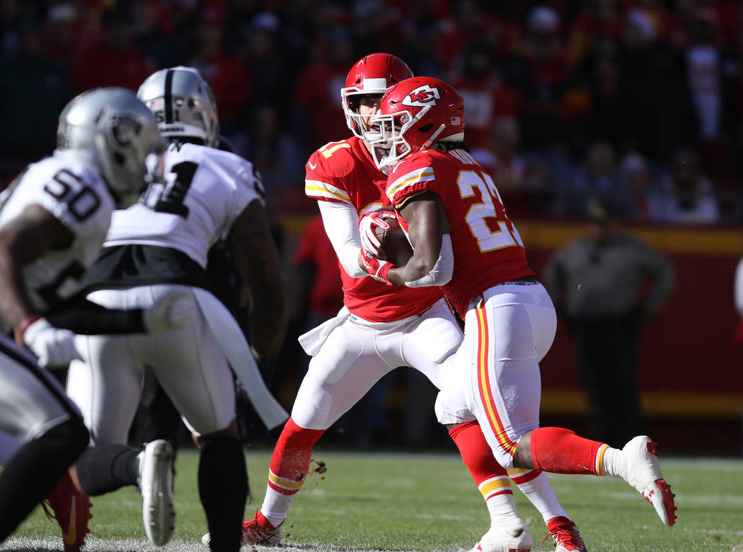 Kansas City Chiefs quarterback Alex Smith (11) hands the football off to Kansas City Chiefs running back Kareem Hunt (27) during the first half of a NFL game in Kansas City, Mo., Sunday, Dec. 10,  ...
