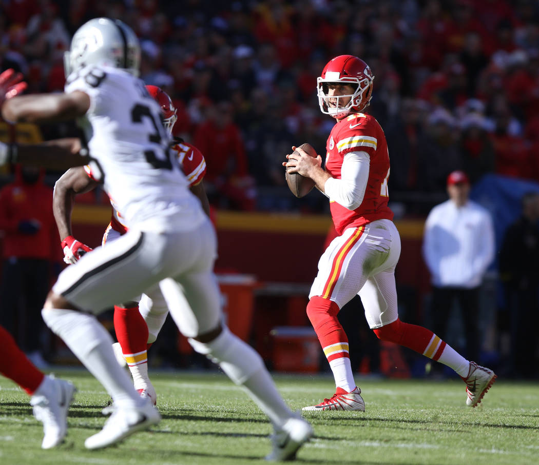 Kansas City Chiefs quarterback Alex Smith (11) looks for an open receiver against the Oakland Raiders during the first half of a NFL game in Kansas City, Mo., Sunday, Dec. 10, 2017. Heidi Fang Las ...