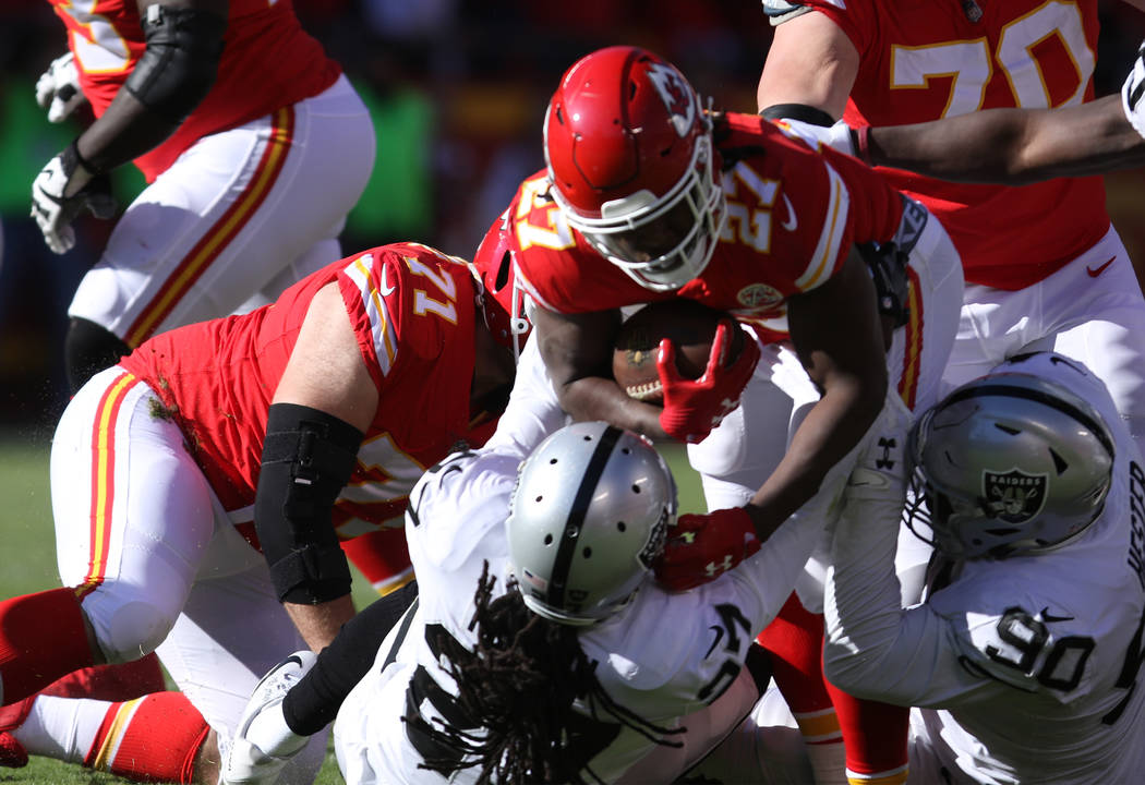Oakland Raiders free safety Reggie Nelson (27) tackles Kansas City Chiefs running back Kareem Hunt (27) during the first half of a NFL game in Kansas City, Mo., Sunday, Dec. 10, 2017. Heidi Fang L ...