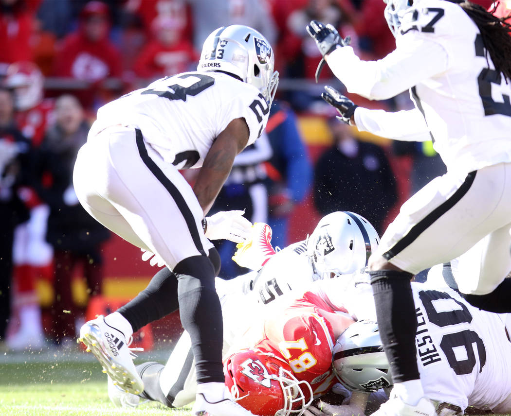 Kansas City Chiefs tight end Travis Kelce (87) is tackled just short of the goal line by Oakland Raiders middle linebacker NaVorro Bowman (53) and defensive tackle Treyvon Hester (90) during the f ...