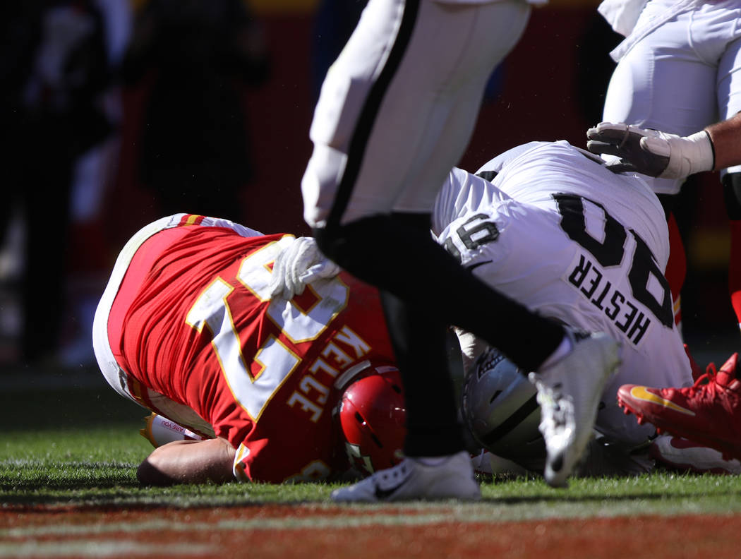 Kansas City Chiefs tight end Travis Kelce (87) is tackled at the Oakland Raiders one yard line by Oakland Raiders defensive tackle Treyvon Hester (90) during the first half of a NFL game in Kansas ...