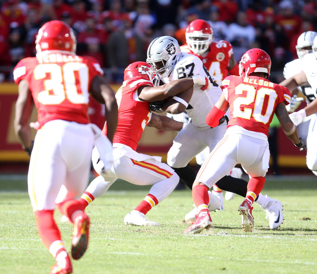 Oakland Raiders tight end Jared Cook (87) catches a pass as Kansas City Chiefs defensive back Steven Terrell (30) tackles him during the first half of a NFL game in Kansas City, Mo., Sunday, Dec.  ...