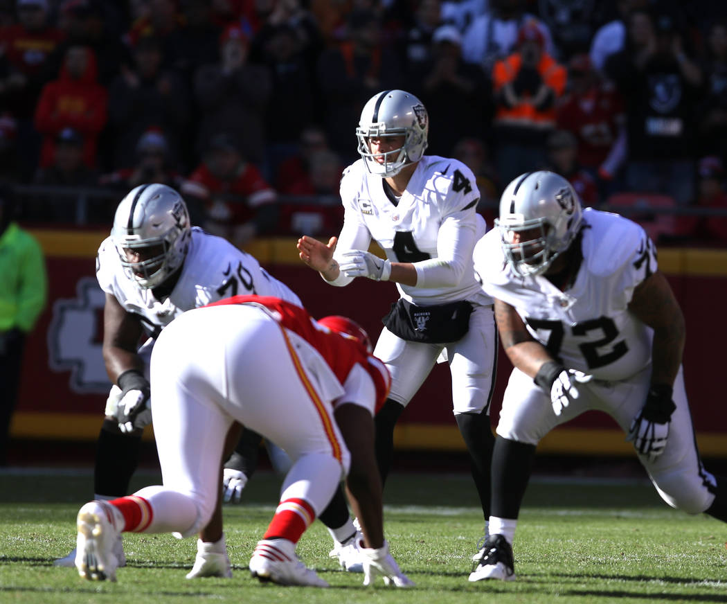 Oakland Raiders quarterback Derek Carr (4) at the line of scrimmage against the Kansas City Chiefs during the first half of a NFL game in Kansas City, Mo., Sunday, Dec. 10, 2017. Heidi Fang Las Ve ...
