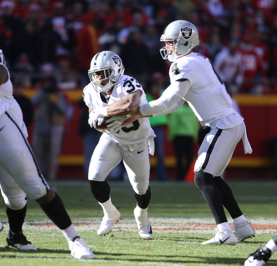 Oakland Raiders quarterback Derek Carr (4) hands off the football to running back DeAndre Washington (33) during the first half of a NFL game in Kansas City, Mo., Sunday, Dec. 10, 2017. Heidi Fang ...