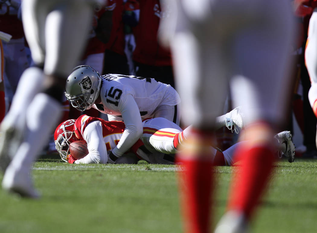 Kansas City Chiefs cornerback Terrance Mitchell (39) intercepts a pass intended for Oakland Raiders wide receiver Michael Crabtree (15) during the first half of a NFL game in Kansas City, Mo., Sun ...