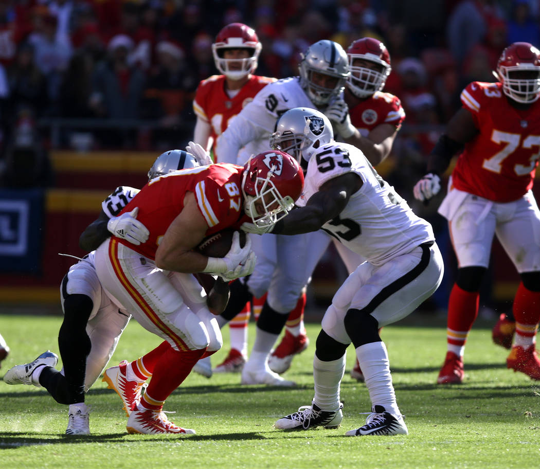 Kansas City Chiefs tight end Travis Kelce (87) catches a pass as Oakland Raiders cornerback Dexter McDonald (23) and middle linebacker NaVorro Bowman (53) try to tackle him during the first half o ...