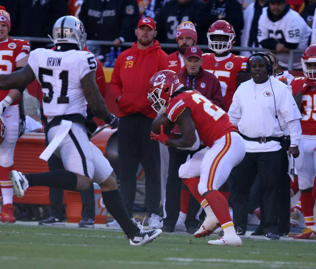 Kansas City Chiefs running back Kareem Hunt (27) catches a pass as Oakland Raiders outside linebacker Bruce Irvin (51) tries to run in for a tackle during the first half of a NFL game in Kansas Ci ...