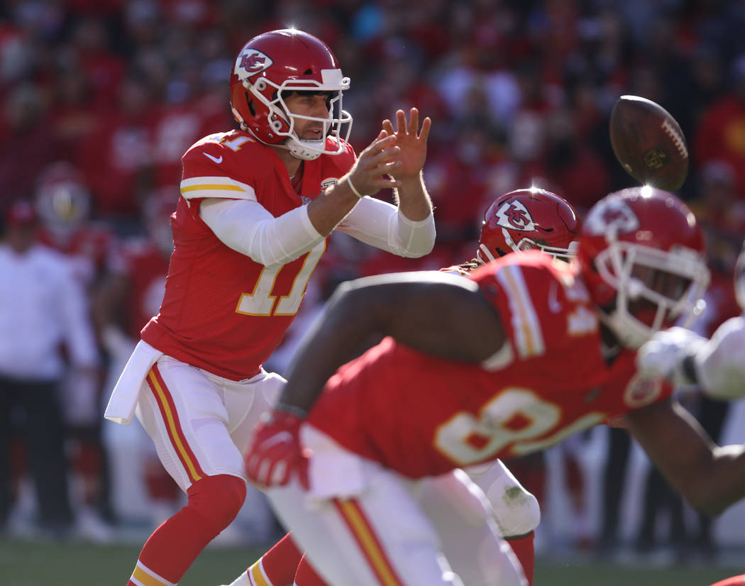 Kansas City Chiefs quarterback Alex Smith (11) gets ready to catch and pass the football after the snap against the Oakland Raiders during the first half of a NFL game in Kansas City, Mo., Sunday, ...