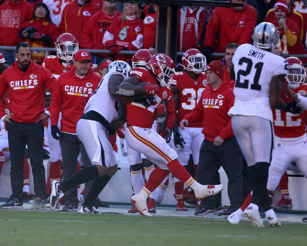 Oakland Raiders outside linebacker Bruce Irvin (51) tries to tackled Kansas City Chiefs running back Kareem Hunt (27) during the first half of a NFL game in Kansas City, Mo., Sunday, Dec. 10, 2017 ...